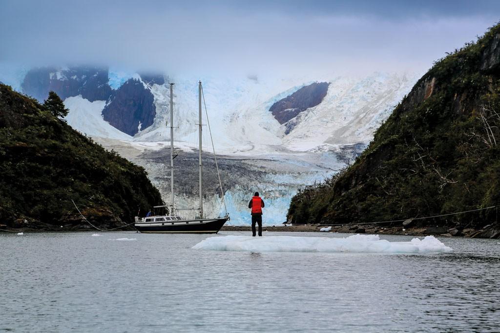 Marcus Fichtner parado sobre un témpano a la deriva. Al fondo, el glaciar Finanlandia occidental, en el fondo del fiordo Brookes, Cordillera Darwin.