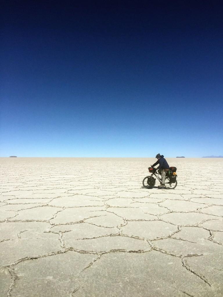 Cielo y tierra en una Ilusión de horizonte de blanco infinito. Joseph Morgan pedalea por Uyuni