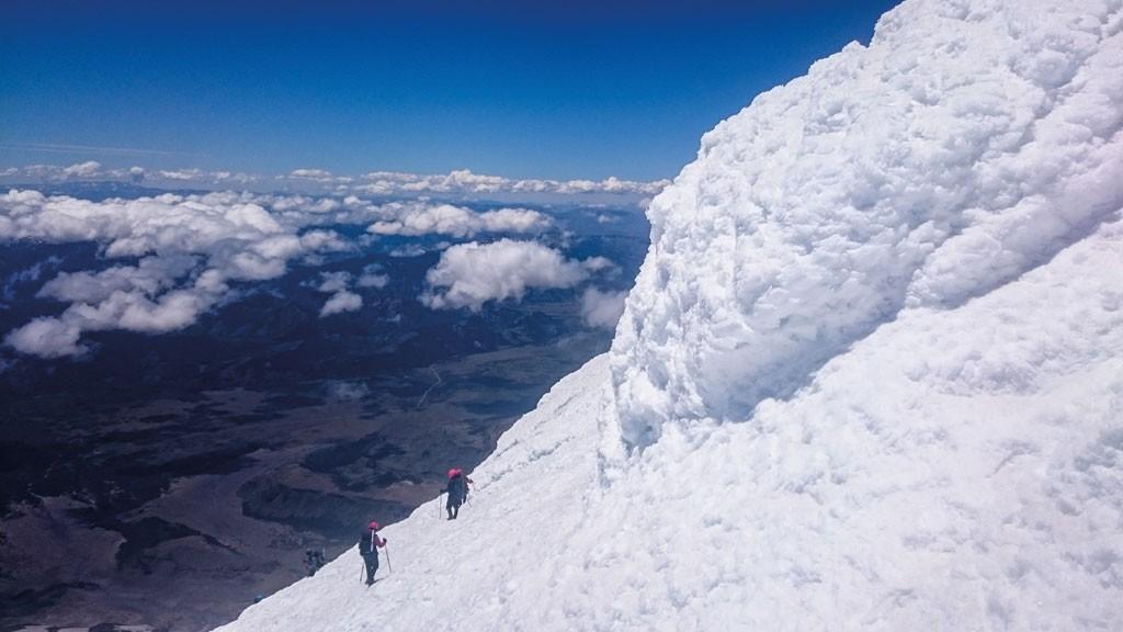 """La imborrable imagen del horizonte y las nubes por debajo de la cumbre del Volcán Lanín, cumbre que se empina hasta los 3.743 m sobre el nivel del mar, en el descenso somos flanqueados por seracs de blanco marmolado. """"Hoy, antes del alba, subí a las montañas, miré los cielos llenos de luminarias y le dije a mi espíritu: Cuando conozcamos todos estos mundos y el placer y la sabiduría que contienen, ¿estaremos tranquilos y satisfechos? Y mi espíritu dijo: No, ganaremos esas alturas sólo para seguir adelante"""" W. Whitman. Foto de Marcelo Noria"""