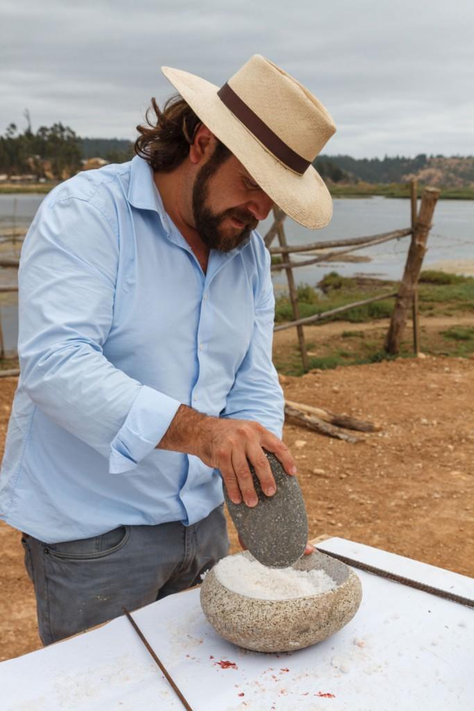 Moliendo un poco la sal de Cáhuil en un mortero para salinar el cordero al palo que se preparará frente a las salinas.